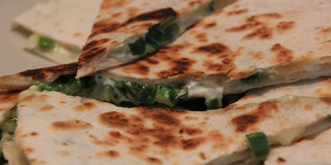 Tortilla wedges with spring onions and wild garlic