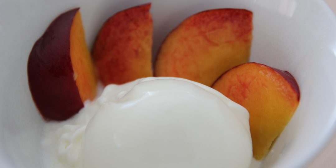 Yoghurt icecream with elder sirup and fresh peach