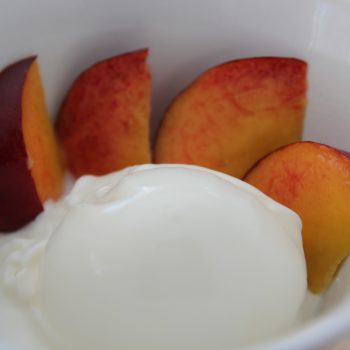 Yoghurt icecream with elder sirup and fresh peach