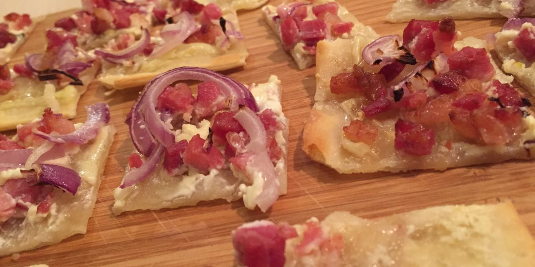 Flammekuche with bacon cubes and onion