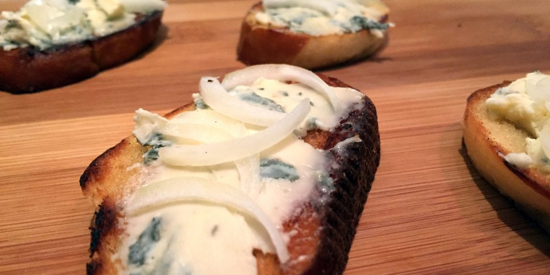Pretzel roll with blue cheese and onions